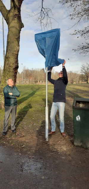 Voorzitter Erik-Jan van Dijk onthult het straatnaambord, links kijkt wethouder Herman van Wanrooij toe.